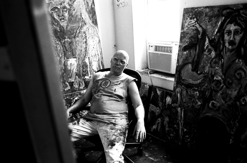 Photograph of Jonathan Herbert studying a painting in progress.